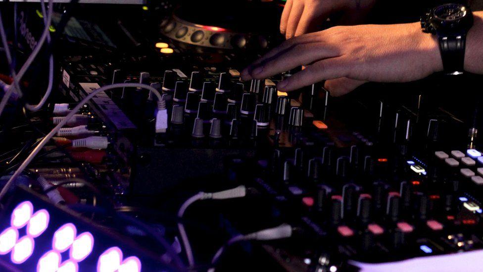 A DJ mixes dance music at a club
