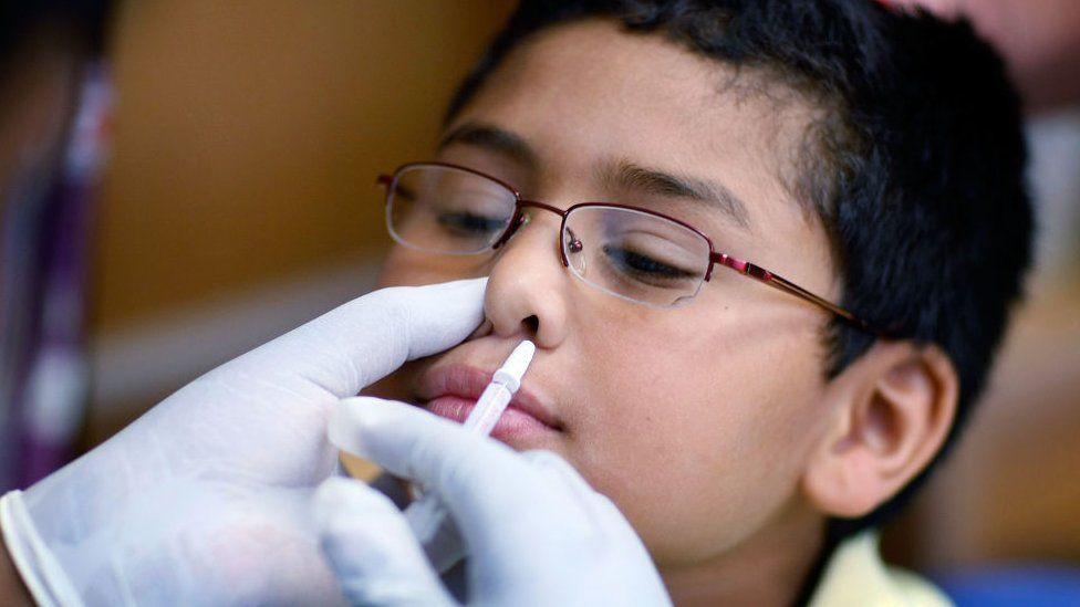 Child getting vaccine spray
