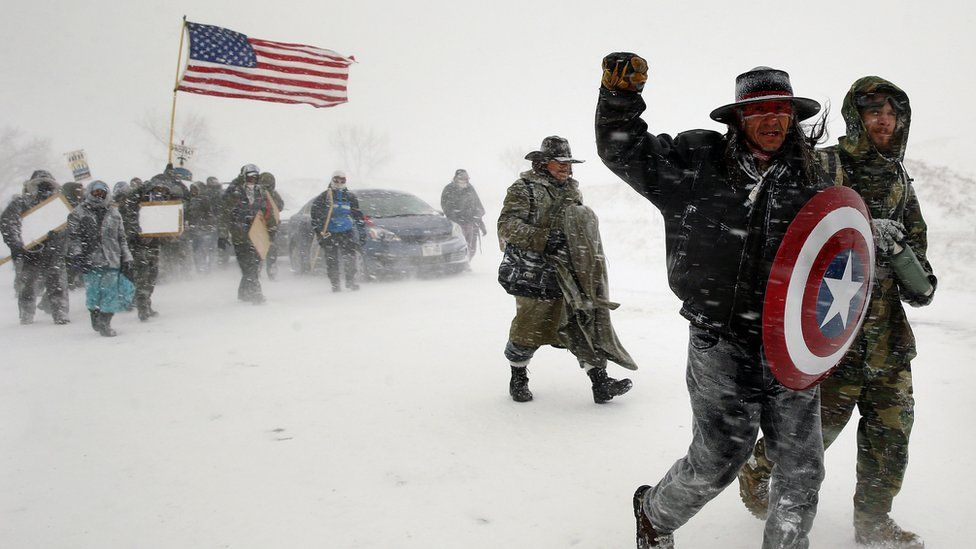 """Veterans join activists in a march to Backwater Bridge just outside the Oceti Sakowin camp during a snow fall as """"water protectors"""""""