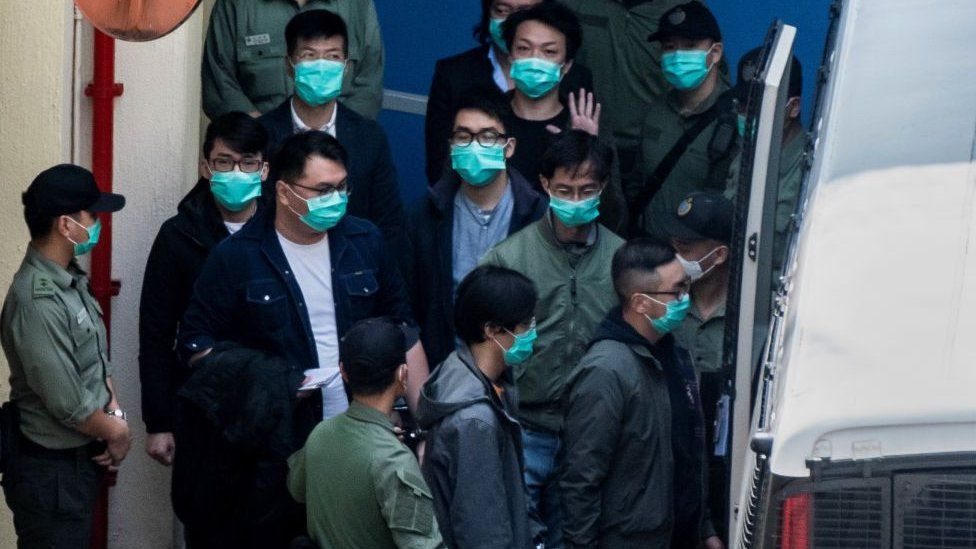 Hong Kong pro-democracy activists are escorted into a van as they leave the Lai Chi Kok