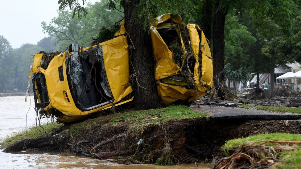 A van crushed by the torrents is pressed against a tree in Germany