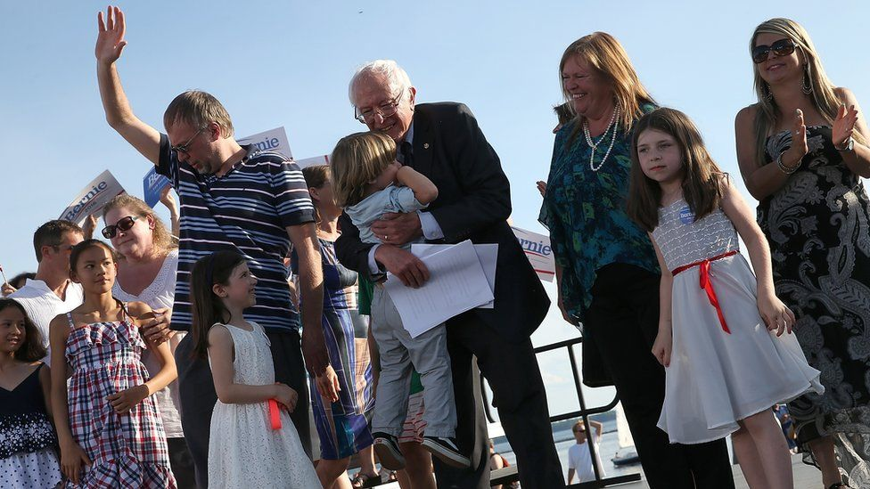 Sanders hugs one of his grandchildren onstage