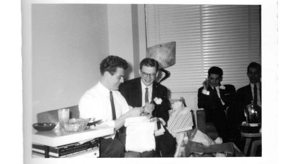 Men open gifts at a wedding