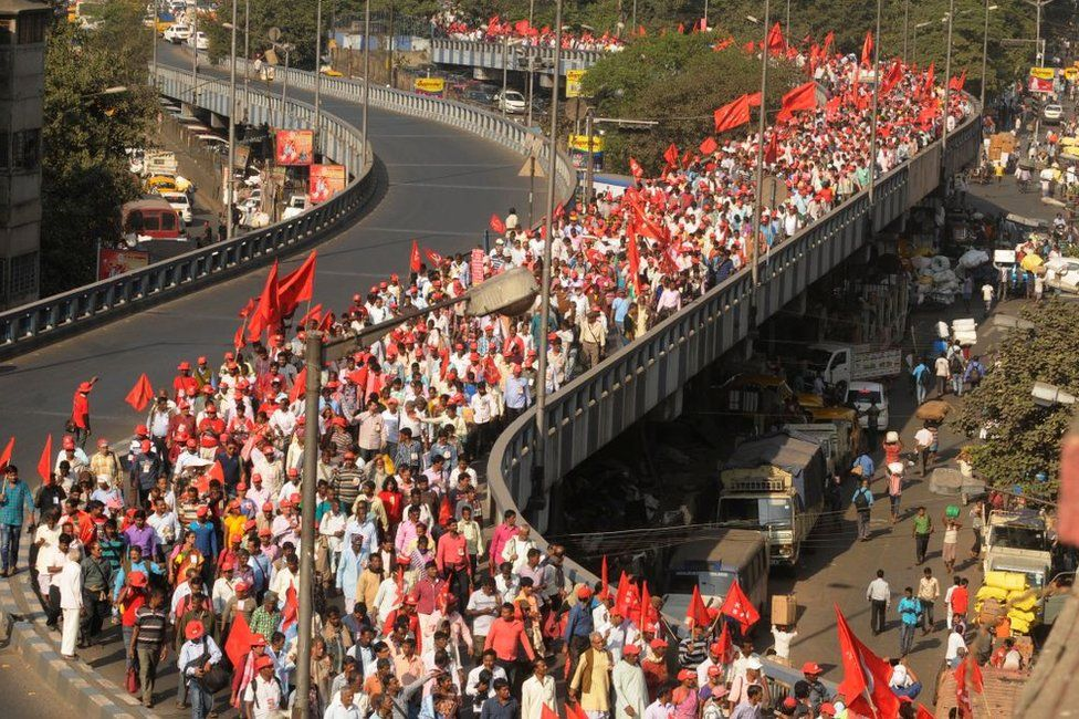 Farmers wave flags and raise slogans as they participate in a protest march organised by Left Front from Singur to Raj Bhawan over their various demands, at Howrah Bridge crossing, on November 29, 2018 in Kolkata, India.