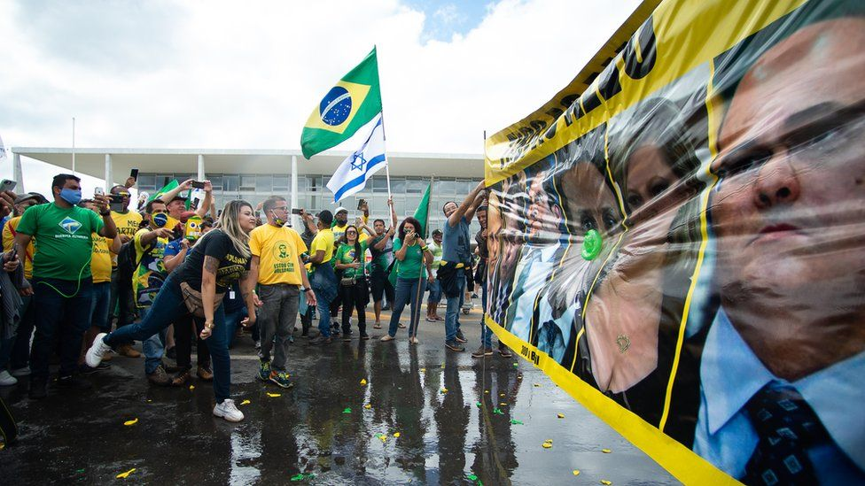 Supporters of Brazilian President Jair Bolsonaro throw water balloons during a protest against lockdown measures