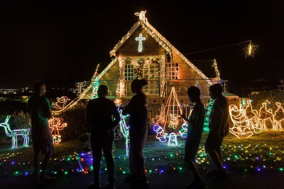People look at a house covered in Christmas lights of various colours.