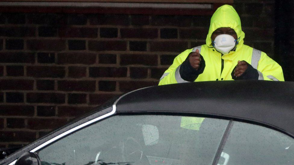 """A security guard wears a surgical mask as he assists a car at a Coronavirus drive-through test centre at Parson""""s Green Medical Centre in London"""