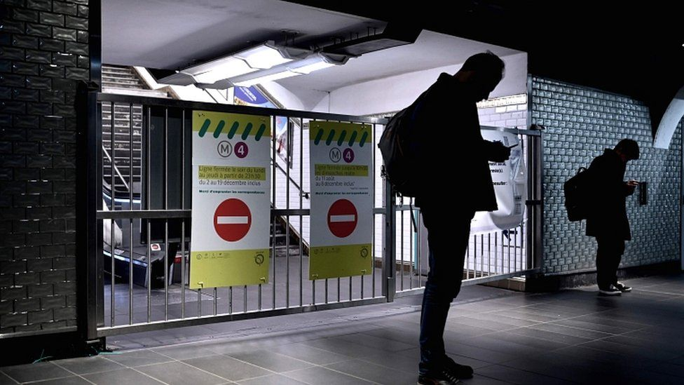 Passengers stand in front of the closed gates of the Châtelet metro station in Paris on 10 December 2019