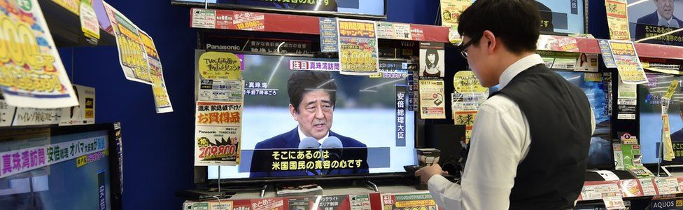 An employee in Japan at an electronics retail store checks televisions displaying news coverage of Japanese Prime Minister Shinzo Abe's visit to Hawaii - 28 December 2016