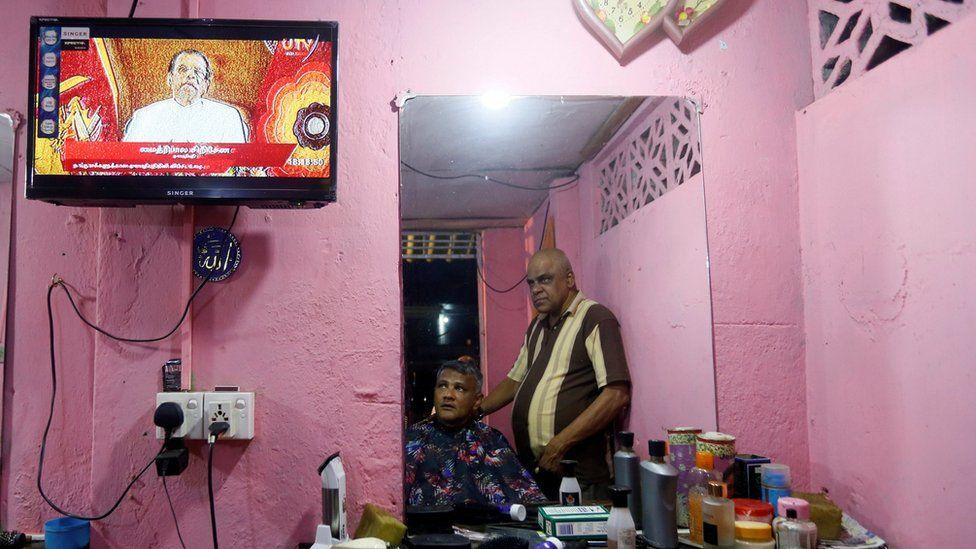Two men watch Mr Sirisena's speech