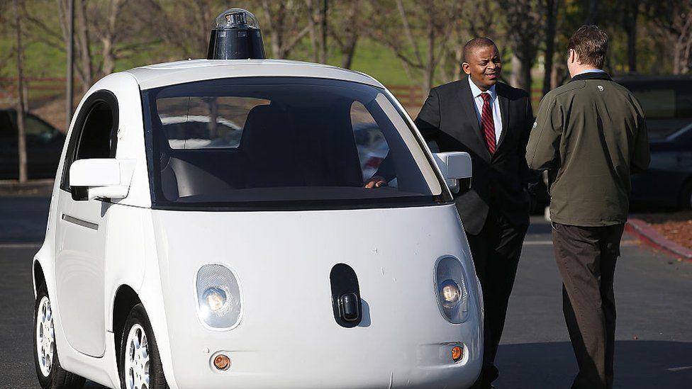 US Transportation Secretary Anthony Foxx inspects a Google self-driving car at the Google headquarters