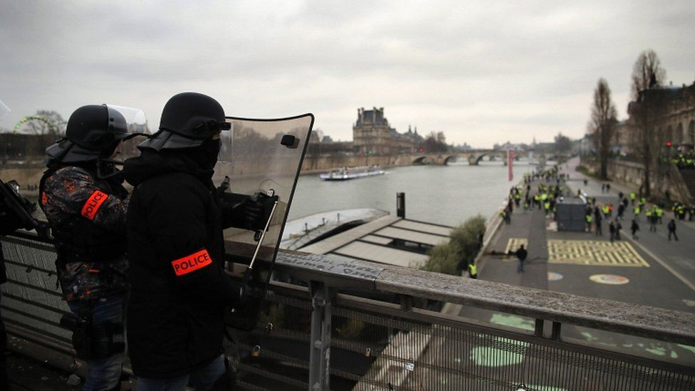 """French riot police stand guard on a bridge over the Seine river overlooking protesters below as clashes erupt during a """"yellow vests"""" protest in Paris, on 5 January 2019"""
