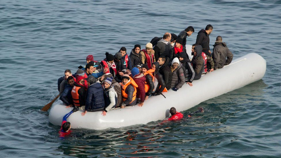 Refugees and migrants arrive in an overloaded rubber dinghy on the Greek island of Lesbos