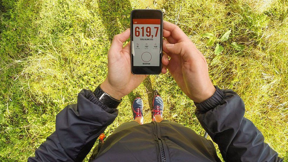 Man holding smartphone with a running app