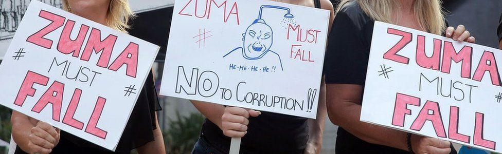 Three women holding placards at a protest calling for South Africa's president to step down.