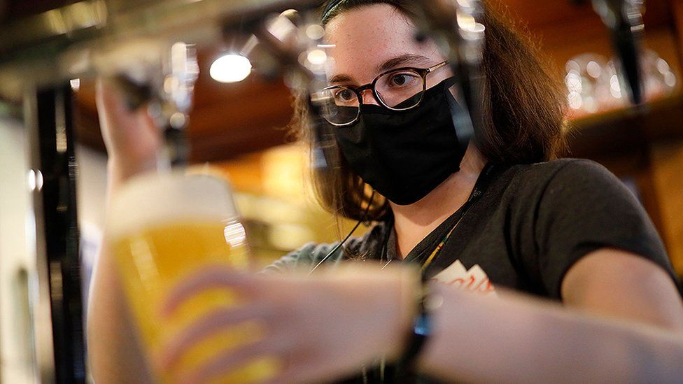 Woman pouring beer wearing a mask