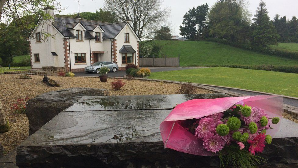 A floral tribute has been placed outside the grounds of the house where Mrs Leonard lived