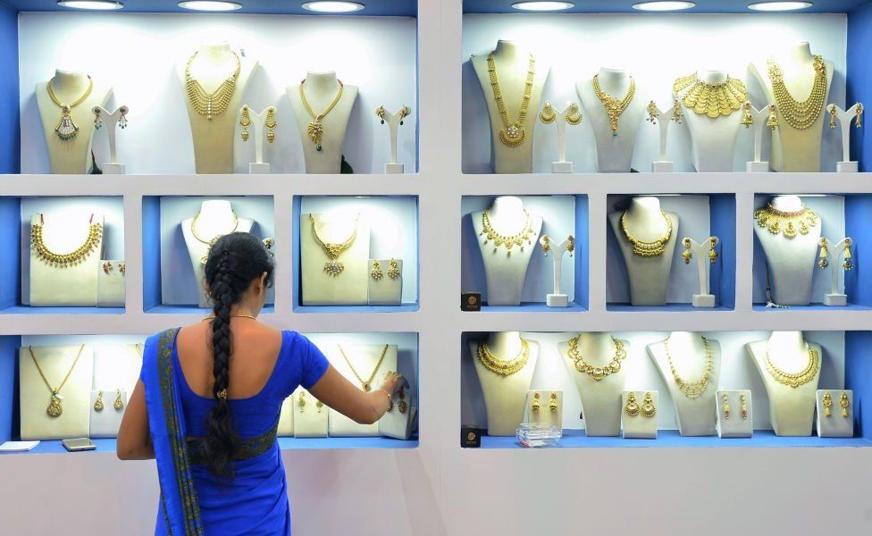 An employee of an Indian jewellery store arranges gold jewellery in Bangalore on 11 August 2017.
