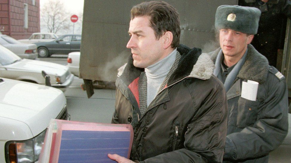 Military journalist Grigori Pasko (L) leaves a car escorted by a militiaman as he arrives at court in Vladivostok 21 January 1999
