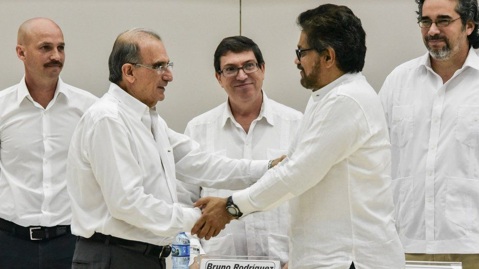 The head of the Colombian government delegation to the peace talks, Humberto de la Calle (L) and the head of the FARC-EP delegation Ivan Marquez (R) shake hands after the signing of the agreement on victims of the conflict at Convention Palace in Havana, on December 15, 2015.