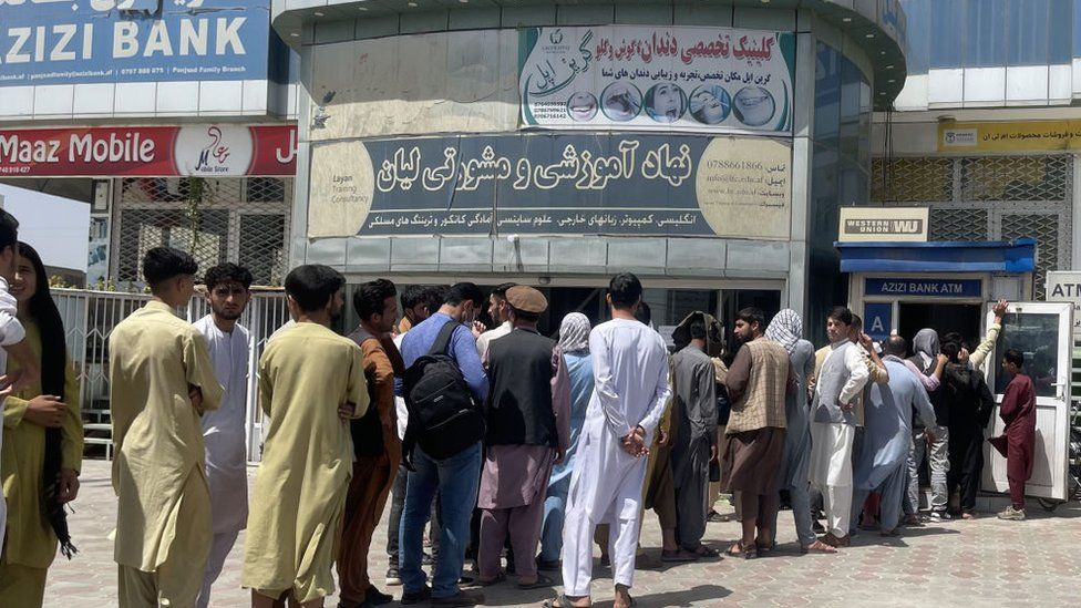 Afghan people line up outside AZIZI Bank to take out cash as the Bank suffers amid money crises in Kabul