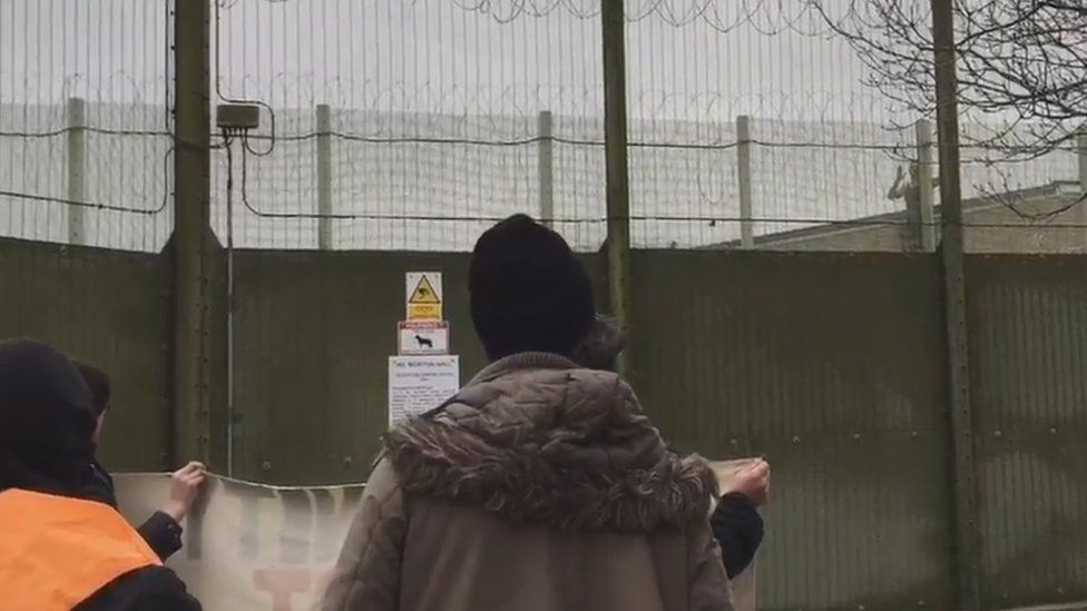 Man climbing a fence inside a detention centre