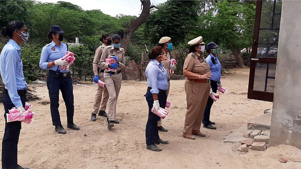 Punjab Police personnel distribute sanitary pads during the lockdown on April 11, 2020 in Bathinda