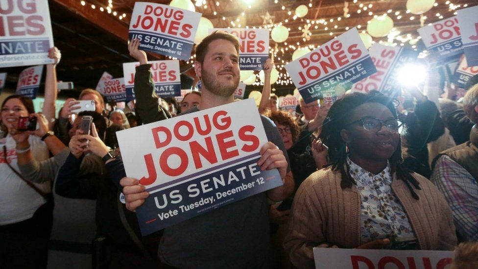 Supporters of Doug Jones listen as he speaks at a rally at Old Car Heaven in Birmingham, Alabama, on 11 December, 2017.