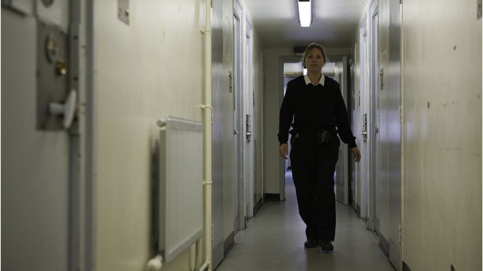 A female prison officer walks down the corridor of a prison's residential wing