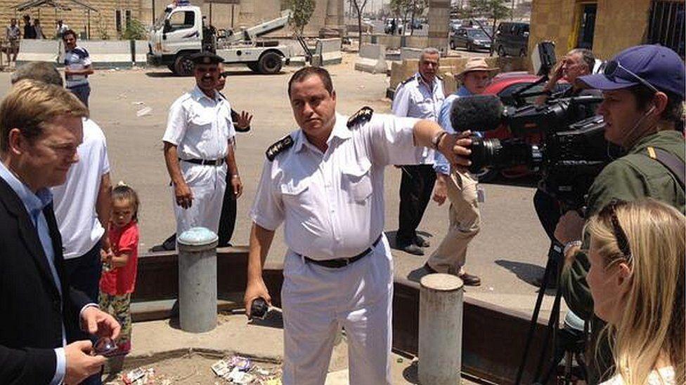 Egyptian policeman covers camera lens as BBC crew films outside Torah Prison