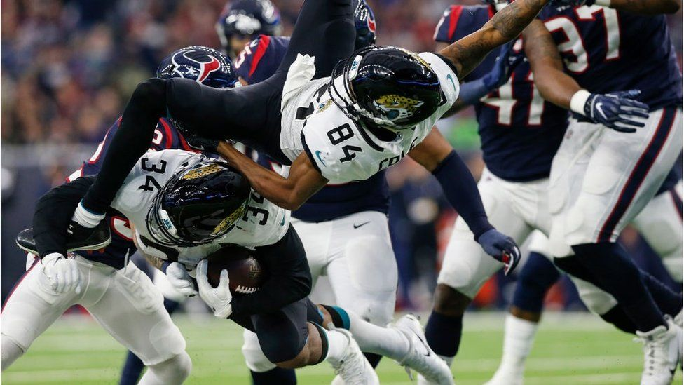 Carlos Hyde #34 of the Jacksonville Jaguars collides with Keelan Cole #84 in the fourth quarter against the Houston Texans at NRG Stadium on December 30, 2018 in Houston, Texas.