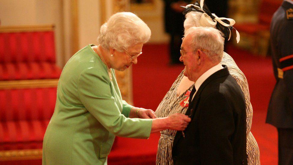 Ronald Jones and Penelope Jones receiving their MBE from Queen Elizabeth II