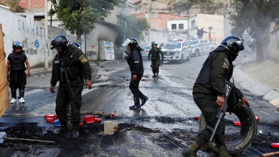 Members of the security forces remove debris from a barricade as they patrol the streets in La Paz