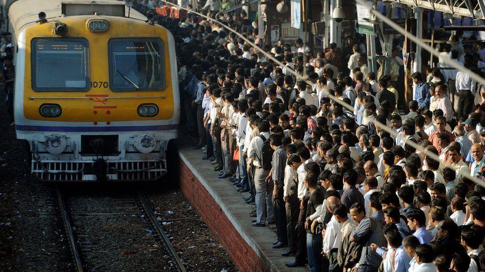 Passengers wait to board a Mumbai local train