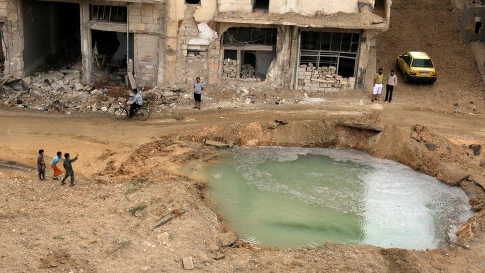 People inspect a hole in the ground filled with water in a damaged site after airstrikes on the rebel held Tariq al-Bab neighbourhood of Aleppo