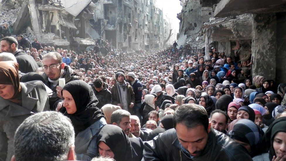 Residents of the Palestinian camp of Yarmouk, queuing to receive food supplies, in Damascus