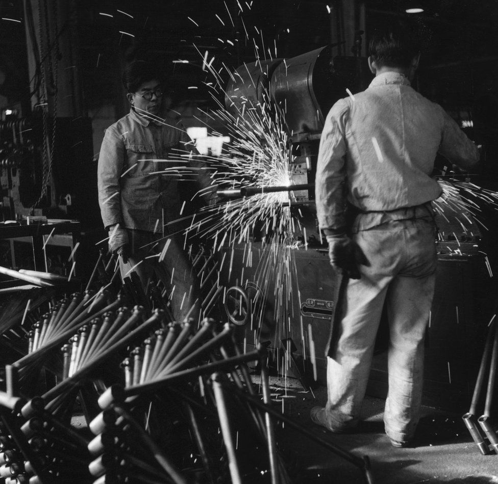Sparks fly off a machine which churns out bicycle frames in a Japanese factory, circa 1953