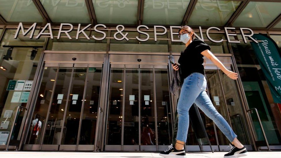 Woman walks by M&S store wearing a face mask