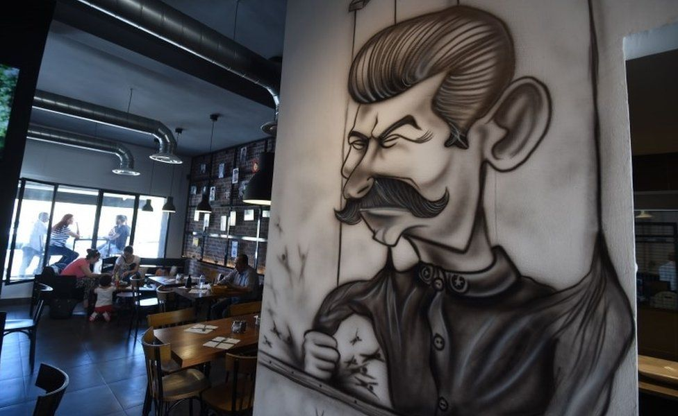 """Cartoons adorn the walls of restaurant """"The Dictator"""" on July 5, 2017 in the upmarket Cite Ennasr suburb of Tunis. A steak named """"Grilled Freedom"""" is just one of many dishes that stand out on the menu of the Tunisian capital""""s """"Le Dictateur"""" restaurant, not a favourite venue for the authorities. Six years after the country's revolution that sparked the Arab Spring, """"Le Dictateur"""" vies for business."""