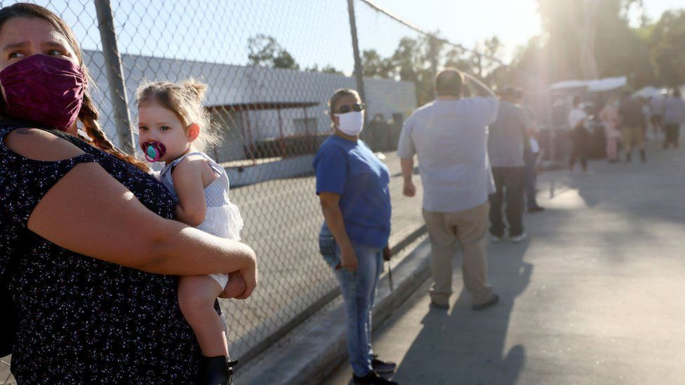 A woman holds her niece while waiting in line at a walk-up Covid-19 testing site on December 2, 2020 in San Fernando, California