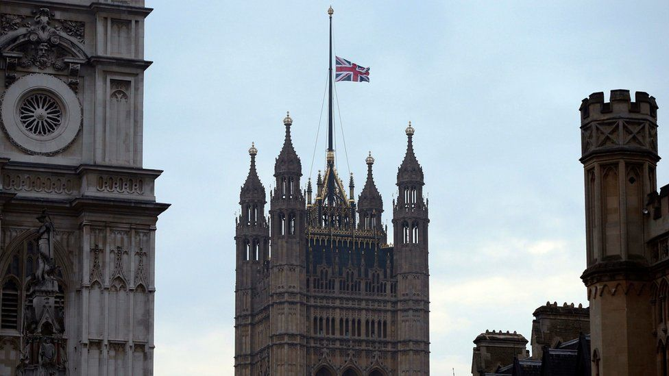 The flag above the Houses of Parliament flies at half mast