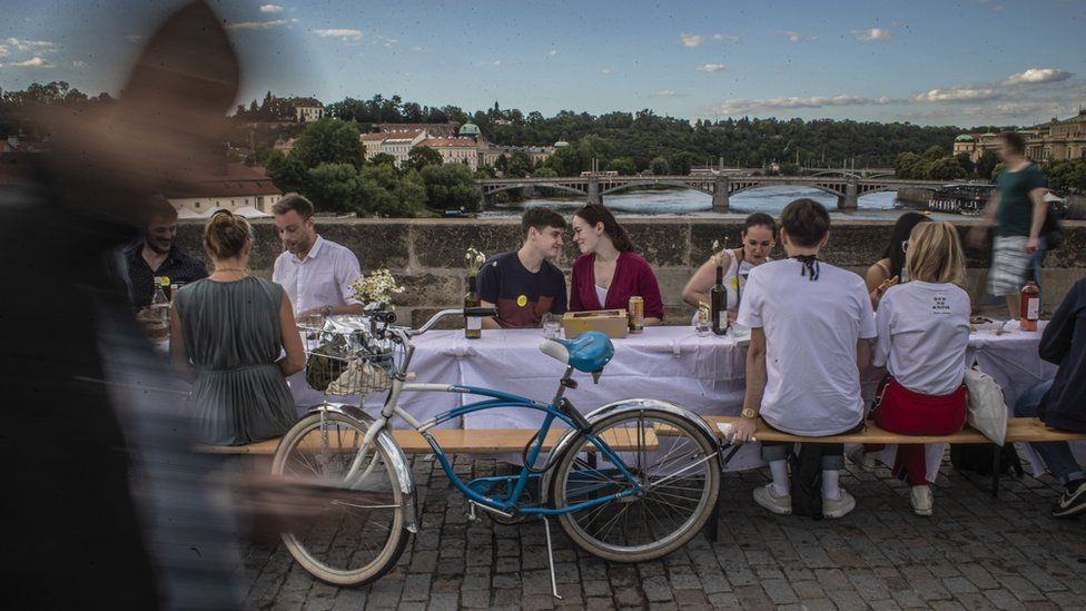 A couple sit at a table on the Charles Bridge in Prague