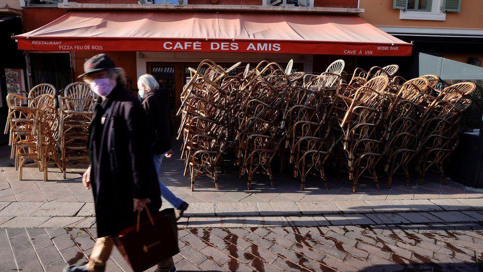 France lockdown - people walking by closed restaurant in Paris