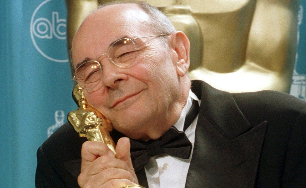 """Stanley Donen, director of the classic films """"Singing In The Rain"""" and """"American in Paris"""", hugs his Oscar backstage"""