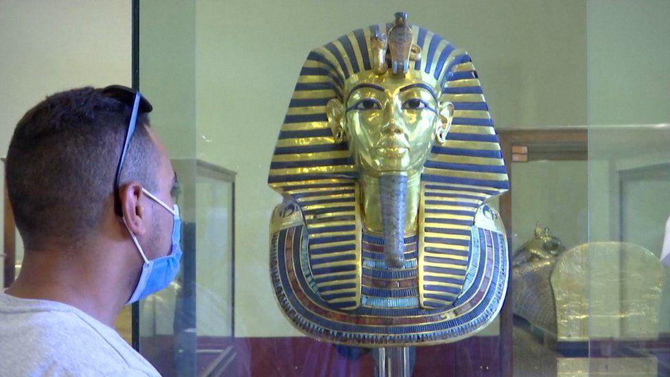 Man wearing a face mask looks at the King Tutankhamun exhibit in Cairo