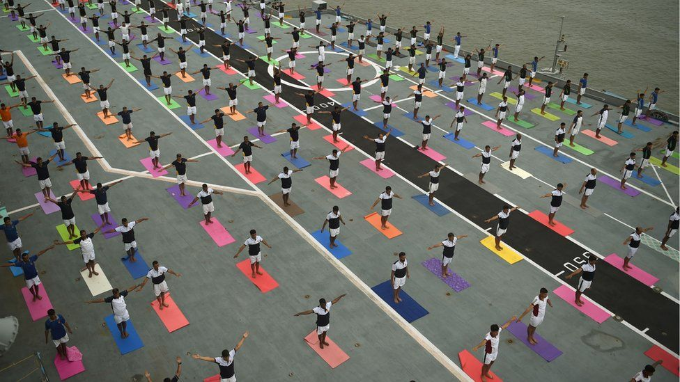 Indian Armed Forces personnel take part in a yoga session to mark International Yoga Day on the Indian Navy aircraft carrier INS Viraat anchored at the Mumbai harbour on June 21, 2017.