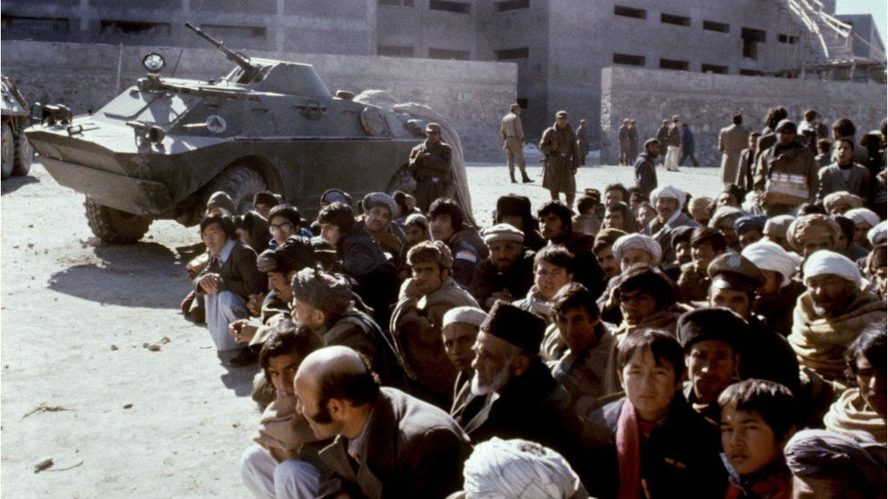 Afghans wait outside the Kabul central Pulicharkhi prison 14 January 1980 days after the Moscow-installed regime of Babrak Karmal took over