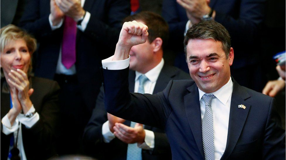 Macedonian Foreign Minister Nikola Dimitrov raises his fist during a signature ceremony of the accession protocol