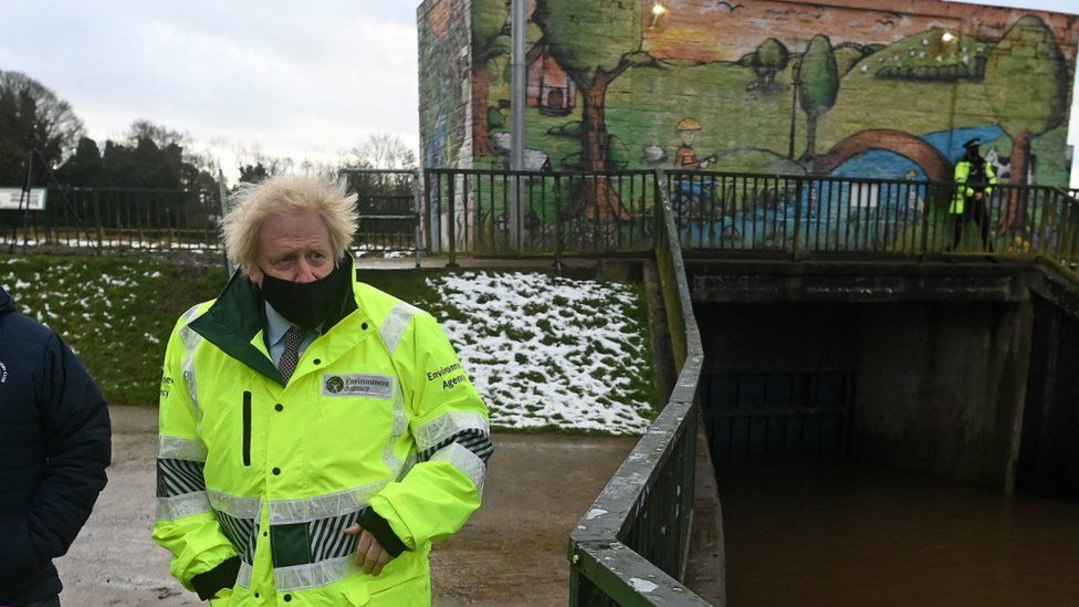 Prime Minister Boris Johnson talks with Environment Agency workers during a visit to a storm basin near the River Mersey in Didsbury