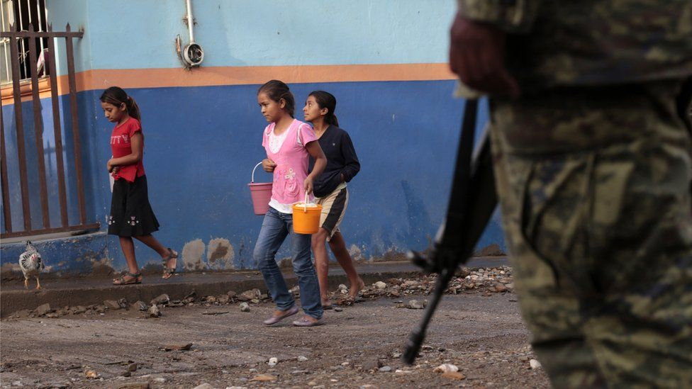 Girls are escorted by soldiers as they walks in Huatla village, Heliodoro Castillo municipality, Guerrero State, Mexico, on 3 August, 2013
